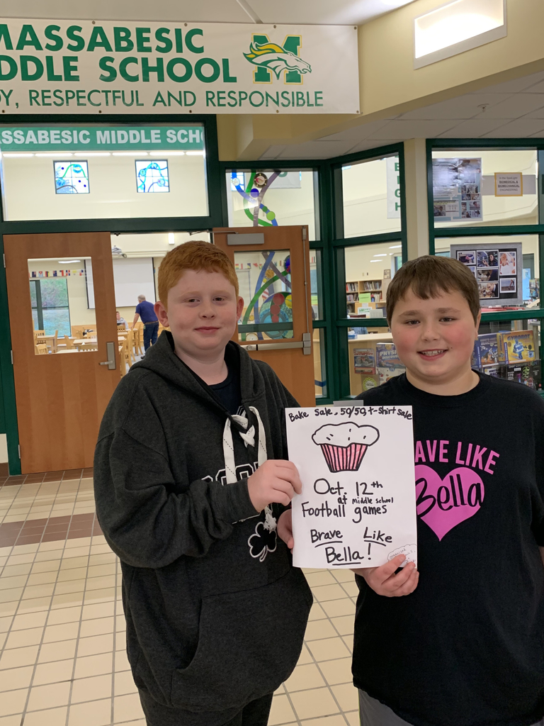 Jaxson Lamb and Zach Sotir, MMS 6th graders, hold a sign for Zach's upcoming fundraiser at the middle school football games on October 12th.