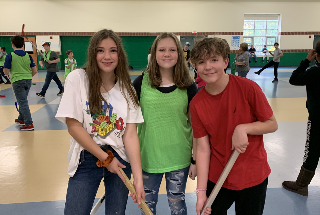 Three middle school students smile while holding floor hockey sticks.