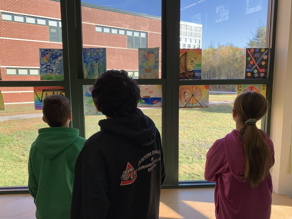Students viewing watercolor artwork hung on the windows of the MMS library.
