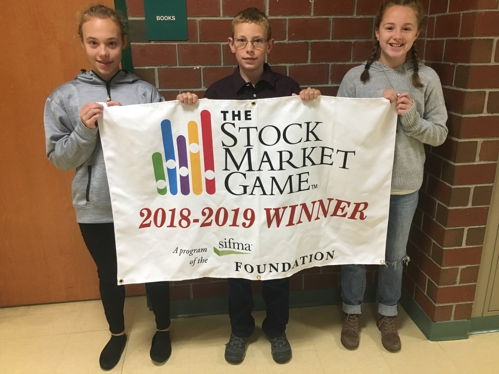Three students holding winning banner for the Stock Market Game