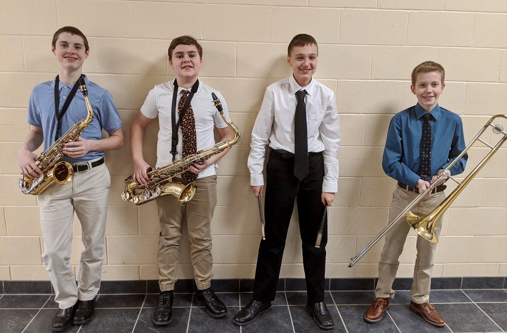 Band students at the honors festival pose with their instruments